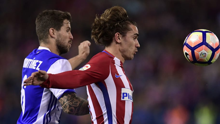 Atletico Madrid's French forward Antoine Griezmann (R) vies with Real Sociedad's defender Inigo Martinez Berridi during the Spanish league football match Club Atletico de Madrid vs Real Sociedad at the Vicente Calderon stadium in Madrid on April 4, 2017. / AFP PHOTO / JAVIER SORIANO        (Photo credit should read JAVIER SORIANO/AFP/Getty Images)