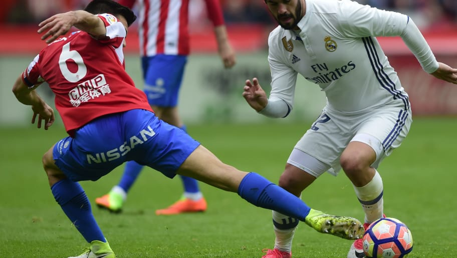 Real Madrid's midfielder Isco (R) vies with Sporting Gijon's Venezuelan defender Fernando Amorebieta during the Spanish league football match Real Sporting de Gijon vs Real Madrid CF at El Molinon stadium in Gijon on April 15, 2017. / AFP PHOTO / MIGUEL RIOPA        (Photo credit should read MIGUEL RIOPA/AFP/Getty Images)