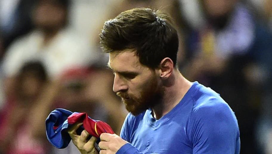 Barcelona's Argentinian forward Lionel Messi looks at his jersey after brandishing it to celebrate his goal during the Spanish league Clasico football match Real Madrid CF vs FC Barcelona at the Santiago Bernabeu stadium in Madrid on April 23, 2017. Barcelona won 3-2. / AFP PHOTO / GERARD JULIEN        (Photo credit should read GERARD JULIEN/AFP/Getty Images)