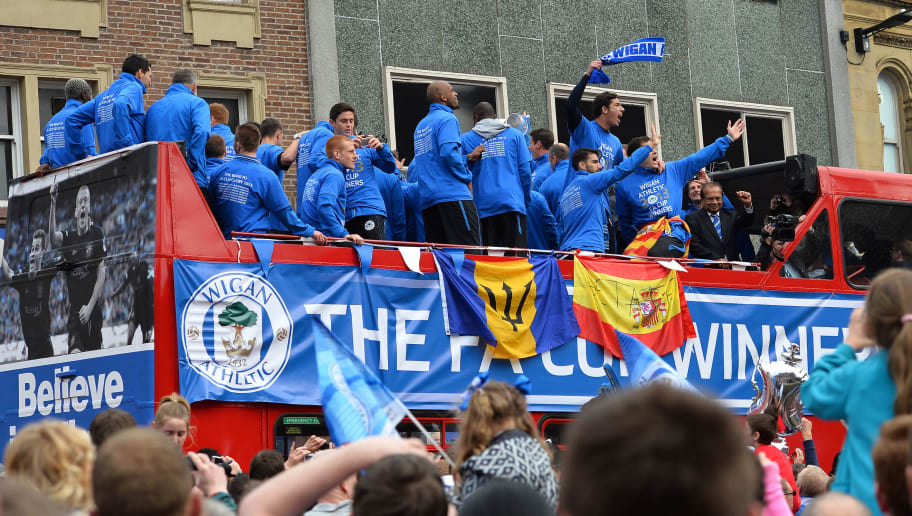 Wigan Athletic players parade in an open top bus through the streets of Wigan in northwest England on May 20, 2013 after they won the English FA Cup. The club paraded the trophy through the town centre despite being relegated from the Premier League the week after their FA Cup victory. AFP PHOTO/Paul Ellis        (Photo credit should read PAUL ELLIS/AFP/Getty Images)