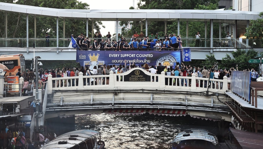 Leicester City football players, staff and owners cross a canal during an open-bus parade in Bangkok on May 19, 2016. Newly-crowned English Premier League champions Leicester City received a royal seal of approval on May 19 at Bangkok's Grand Palace, with the Thai-owned team presenting its trophy to a portrait of the king before a bus parade through the capital. / AFP / LILLIAN SUWANRUMPHA        (Photo credit should read LILLIAN SUWANRUMPHA/AFP/Getty Images)