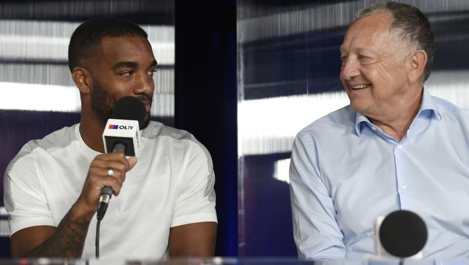 Lyon's French forward Alexandre Lacazette (L) speaks with Lyon's president Jean-Michel Aulas (R) during a press conference on August 8, 2015 in Lyon, southeastern France.  AFP PHOTO / PHILIPPE DESMAZES        (Photo credit should read PHILIPPE DESMAZES/AFP/Getty Images)