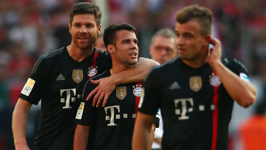 COLOGNE, GERMANY - SEPTEMBER 27: Xabi Alonso (L) hugs Juan Bernat after during the Bundesliga match between 1. FC Koeln and FC Bayern Muenchen at RheinEnergieStadion on September 27, 2014 in Cologne, Germany.  (Photo by Alex Grimm/Bongarts/Getty Images)