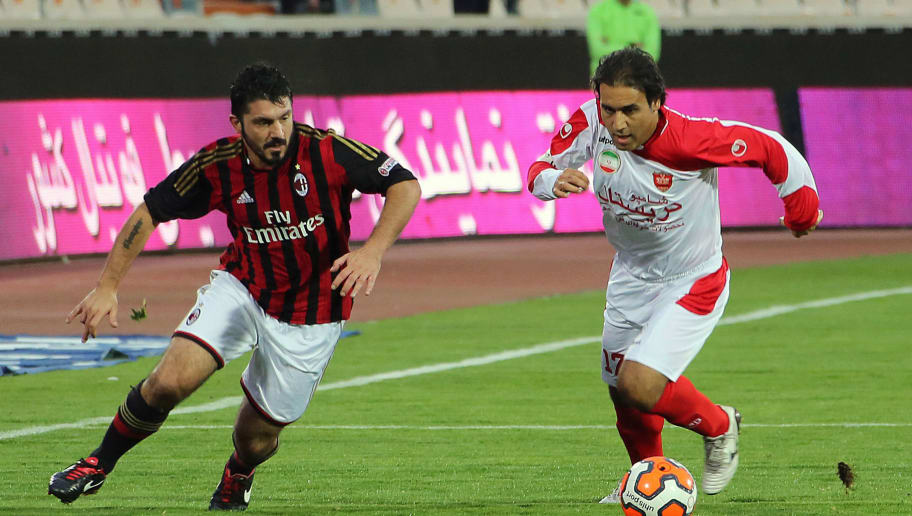 Former AC. Milan player Gennaro Gattuso (L)  defends against former Persepolis player Mehdi Mahdavikia (R) during an exhibition soccer match at the Azadi stadium in Tehran on November 28, 2013. AC.Milan won 3-1. AFP PHOTO / ATTA KENARE        (Photo credit should read ATTA KENARE/AFP/Getty Images)