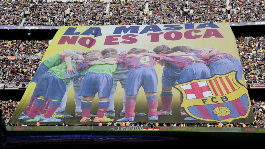 Barcelona's supporters unveil a giant banner reading in Catalan 'La Masia, don't touch it' before the Spanish league football match FC Barcelona vs Real Betis at the Camp Nou stadium in Barcelona.  AFP PHOTO / JOSEP LAGO        (Photo credit should read JOSEP LAGO/AFP/Getty Images)