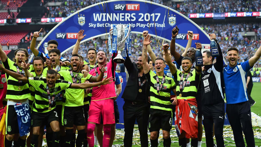 Huddersfield Town's Welsh goalkeeper Danny Ward (centre left) and Huddersfield Town's German head coach David Wagner (centre right) hold up the Championship Playoff trophy as Huddersfield's players celebrate winning the penalty shoot-out on the pitch after the English Championship play-off final football match between Huddersfield Town and Reading at Wembley Stadium in London on May 29, 2017. Huddersfield won the penalty shoot-out 4-3 after the game finished 0-0 after extra time. / AFP PHOTO / Glyn KIRK / NOT FOR MARKETING OR ADVERTISING USE / RESTRICTED TO EDITORIAL USE        (Photo credit should read GLYN KIRK/AFP/Getty Images)