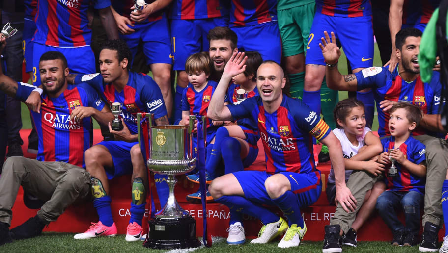 Barcelona's midfielder Andres Iniesta (C) and teammates celebrate their victory past the trophy after the team won the Spanish Copa del Rey (King's Cup) final football match FC Barcelona vs Deportivo Alaves at the Vicente Calderon stadium in Madrid on May 27, 2017. Barcelona won 3-1. / AFP PHOTO / Josep LAGO        (Photo credit should read JOSEP LAGO/AFP/Getty Images)