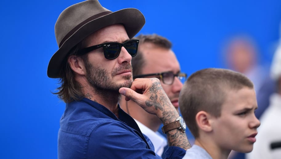 Former England football captain David Beckham and his son Romeo watch Australia's Jordan Thompson playing against Sam Querrey of the US in the second round of the men's singles at the ATP Aegon Championships tennis tournament at the Queen's Club in west London on June 22, 2017. / AFP PHOTO / GLYN KIRK        (Photo credit should read GLYN KIRK/AFP/Getty Images)