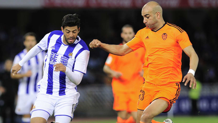Real Sociedad's Mexican forward Carlos Vela (L) vies with Valencia's Tunisian defender Aymen Abdennour (R) during the Spanish league football match Real Sociedad vs Valencia CF at the Anoeta stadium in San Sebastian on December 10, 2016. / AFP / ANDER GILLENEA        (Photo credit should read ANDER GILLENEA/AFP/Getty Images)