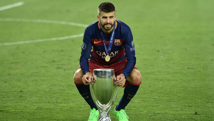 Barcelona's Spanish defender Gerard Pique celebrates with the trophy after winning the UEFA Super Cup final football match between FC Barcelona and Sevilla FC on August 11, 2015 at the Boris Paichadze Dinamo Arena in Tbilisi. AFP PHOTO / KIRILL KUDRYAVTSEV        (Photo credit should read KIRILL KUDRYAVTSEV/AFP/Getty Images)