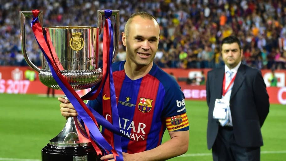 Barcelona's midfielder Andres Iniesta holds up the trophy after the team won the Spanish Copa del Rey (King's Cup) final football match FC Barcelona vs Deportivo Alaves at the Vicente Calderon stadium in Madrid on May 27, 2017. Barcelona won 3-1. / AFP PHOTO / Ander GILLENEA        (Photo credit should read ANDER GILLENEA/AFP/Getty Images)