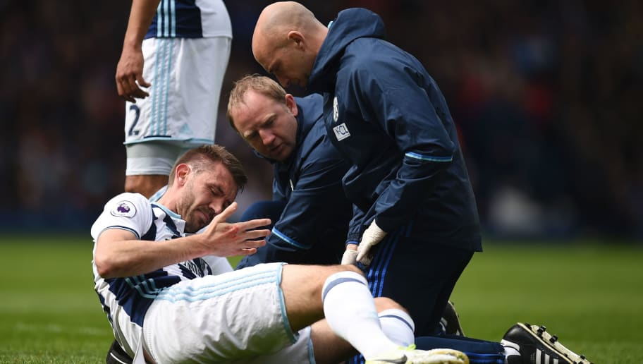 West Bromwich Albion's Northern Irish defender Gareth McAuley has a head wound dressed on the pitch after a coming together during the English Premier League football match between West Bromwich Albion and Leicester City at The Hawthorns stadium in West Bromwich, central England, on April 29, 2017.  / AFP PHOTO / Oli SCARFF / RESTRICTED TO EDITORIAL USE. No use with unauthorized audio, video, data, fixture lists, club/league logos or 'live' services. Online in-match use limited to 75 images, no video emulation. No use in betting, games or single club/league/player publications.  /         (Photo credit should read OLI SCARFF/AFP/Getty Images)