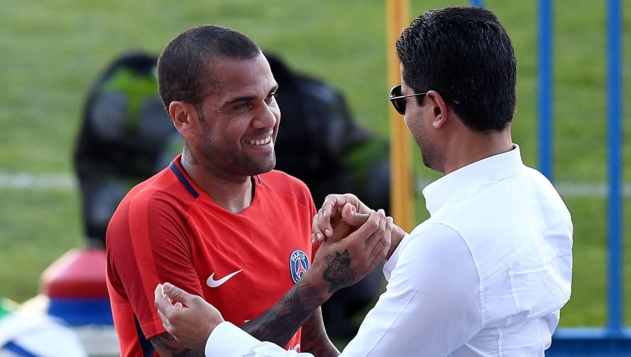 Paris Saint-Germain's Qatari president Nasser Al-Khelaifi (R) speaks with Paris Saint-Germain's Brazilian defender Dani Alves at the end of a training session at the Grand Stade in Tangiers on July 28, 2017 on the eve of the French Trophy of Champions (Trophee des Champions) football match between Paris Saint-Germain and Monaco. / AFP PHOTO / FRANCK FIFE        (Photo credit should read FRANCK FIFE/AFP/Getty Images)
