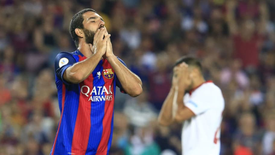 Barcelona's Turkish midfielder Arda Turan (C) reacts to missing a goal opportunity during the second leg of the Spanish Supercup football match between FC Barcelona and Sevilla FC at the Camp Nou stadium in Barcelona on August 17, 2016. / AFP / PAU BARRENA        (Photo credit should read PAU BARRENA/AFP/Getty Images)
