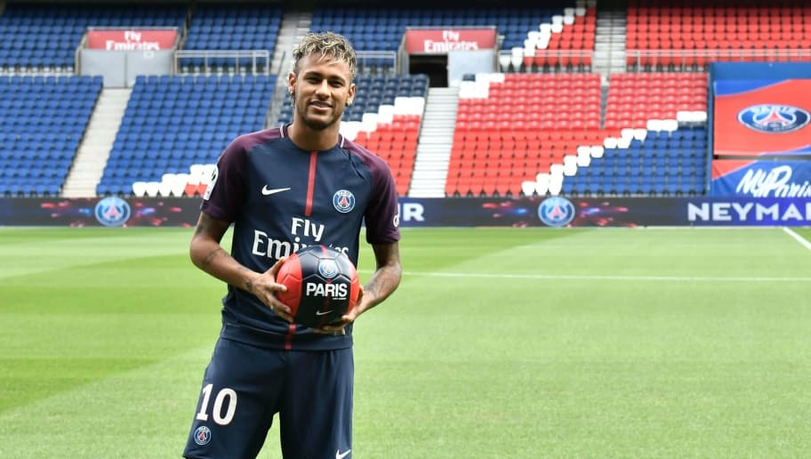 TOPSHOT - Brazilian superstar Neymar poses with a ball during his official presentation at the Parc des Princes stadium on August 4, 2017 in Paris after agreeing a five-year contract following his world record 222 million euro ($260 million) transfer from Barcelona to Paris Saint Germain's (PSG). Paris Saint-Germain have signed Brazilian forward Neymar from Barcelona for a world-record transfer fee of 222 million euros (around $264 million), more than doubling the previous record. Neymar said he came to Paris Saint-Germain for a 'bigger challenge' in his first public comments since arriving in the French capital. / AFP PHOTO / PHILIPPE LOPEZ        (Photo credit should read PHILIPPE LOPEZ/AFP/Getty Images)