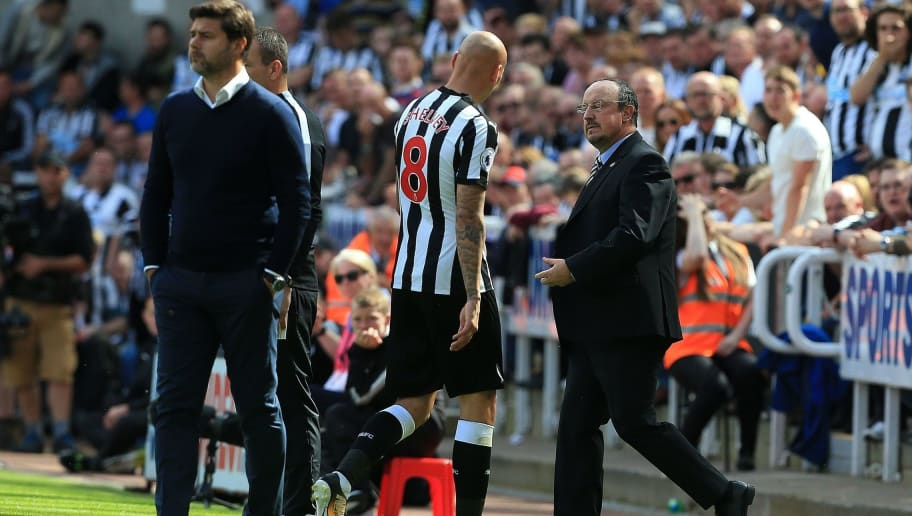Newcastle United's English midfielder Jonjo Shelvey (C) passes Tottenham Hotspur's Argentinian head coach Mauricio Pochettino (L) and Newcastle United's Spanish manager Rafael Benitez as he leaves the pitch after receiving a red card during the English Premier League football match between Newcastle United and Totenham Hotspur at St James' Park in Newcastle-upon-Tyne, north east England on August 13, 2017. / AFP PHOTO / Lindsey PARNABY / RESTRICTED TO EDITORIAL USE. No use with unauthorized audio, video, data, fixture lists, club/league logos or 'live' services. Online in-match use limited to 75 images, no video emulation. No use in betting, games or single club/league/player publications.  /         (Photo credit should read LINDSEY PARNABY/AFP/Getty Images)
