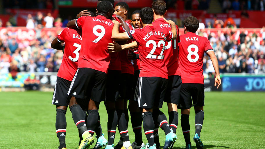 Manchester United's Ivorian defender Eric Bailly celebrates with teammates  scoring the team's first goal during the English Premier League football match between Swansea City and Manchester United at The Liberty Stadium in Swansea, south Wales on August 19, 2017. / AFP PHOTO / Geoff CADDICK / RESTRICTED TO EDITORIAL USE. No use with unauthorized audio, video, data, fixture lists, club/league logos or 'live' services. Online in-match use limited to 75 images, no video emulation. No use in betting, games or single club/league/player publications.  /         (Photo credit should read GEOFF CADDICK/AFP/Getty Images)