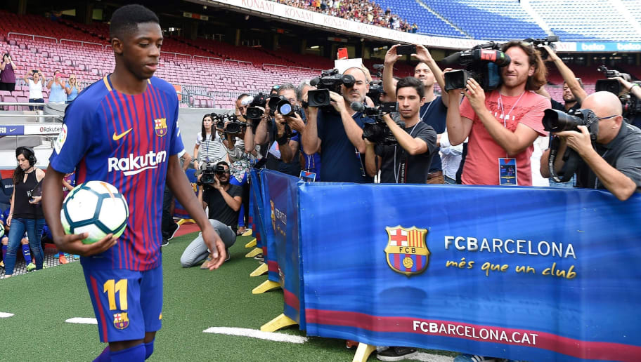 Barcelona's new player Ousmane Dembele (L) enters the pitch at the Camp Nou stadium in Barcelona, during his official presentation by the Catalan football club, on August 28, 2017. French starlet Ousmane Dembele agreed a five-year deal with Barcelona worth 105 million euros ($125 million) plus add-ons. Dembele, 20, moves from Borussia Dortmund, where he has been suspended since he boycotted training on August 10 in protest after the German club rejected Barca's first bid.  / AFP PHOTO / LLUIS GENE        (Photo credit should read LLUIS GENE/AFP/Getty Images)