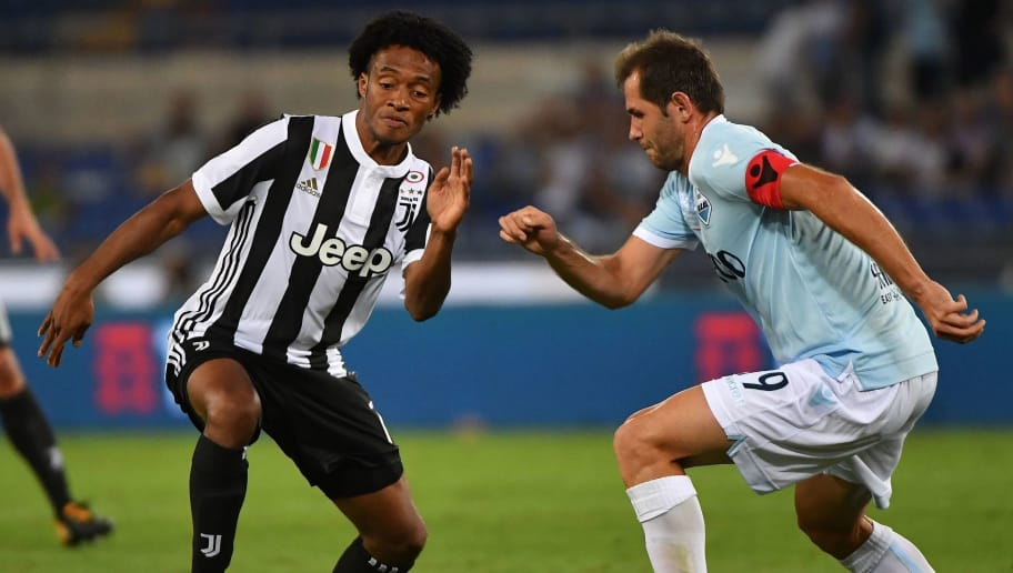 Lazio's midfielder from Bosnia-Herzegovina Senad Lulic (R) fights for the ball with  Juventus's midfielder from Colombia Juan Cuadrado during the Italian SuperCup TIM football match Juventus vs lazio on August 13, 2017 at the Olympic stadium in Rome.  / AFP PHOTO / ALBERTO PIZZOLI        (Photo credit should read ALBERTO PIZZOLI/AFP/Getty Images)