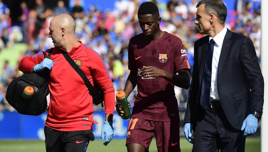 Barcelona's forward from France Ousmane Dembele (C) walks with the team's doctor during the Spanish league football match Getafe CF vs FC Barcelona at the Col. Alfonso Perez stadium in Getafe on September 16, 2017. / AFP PHOTO / PIERRE-PHILIPPE MARCOU        (Photo credit should read PIERRE-PHILIPPE MARCOU/AFP/Getty Images)