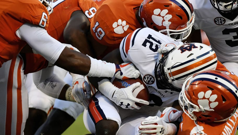 CLEMSON, SC - SEPTEMBER 09:  Defensive back K'Von Wallace #12, safety Tanner Muse #19, and linebacker Dorian O'Daniel #6 of the Clemson Tigers group tackle wide receiver Eli Stove #12 of the Auburn Tigers during the football game at Memorial Stadium on September 9, 2017 in Clemson, South Carolina. (Photo by Mike Comer/Getty Images)