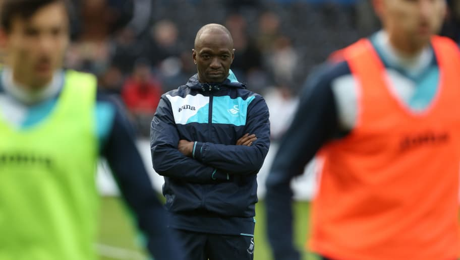 Swansea City's French assistant manager Claude Makelele (C) watches the players warm up ahead of the English Premier League football match between Swansea City and Arsenal at The Liberty Stadium in Swansea, south Wales on January 14, 2017. / AFP / Geoff CADDICK / RESTRICTED TO EDITORIAL USE. No use with unauthorized audio, video, data, fixture lists, club/league logos or 'live' services. Online in-match use limited to 75 images, no video emulation. No use in betting, games or single club/league/player publications.  /         (Photo credit should read GEOFF CADDICK/AFP/Getty Images)