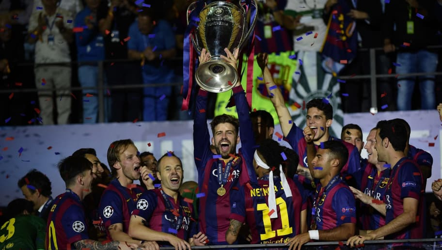 Barcelona's defender Gerard Pique raises the trophy next to Barcelona's Croatian midfielder Ivan Rakitic (2L) and Barcelona's midfielder Andres Iniesta (3L) the UEFA Champions League Final football match between Juventus Torino and FC Barcelona at the Olympic Stadium in Berlin on June 6, 2015. AFP PHOTO / OLIVIER MORIN        (Photo credit should read OLIVIER MORIN/AFP/Getty Images)