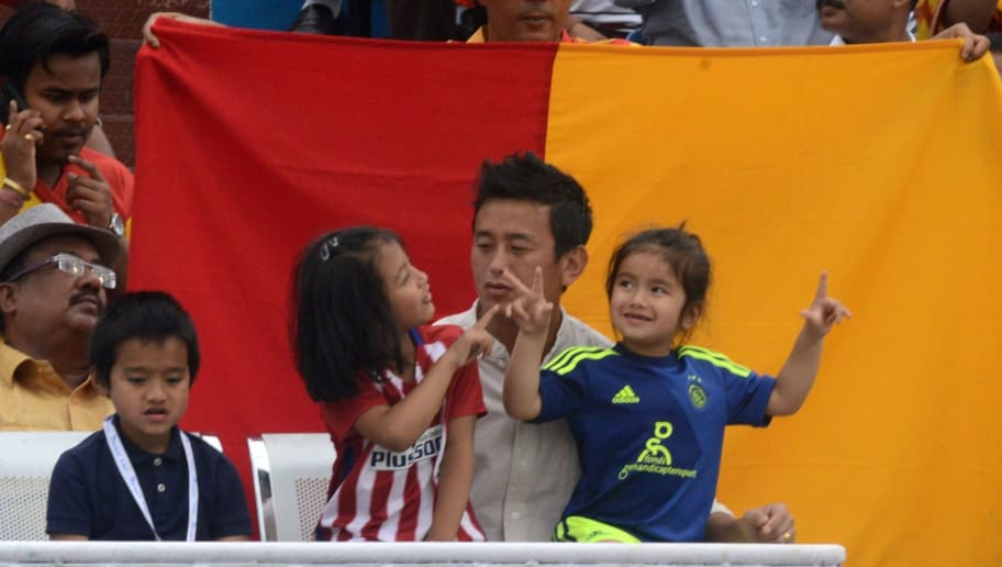 Former Indian football team captain and Trinamool Congress candidate for Darjeeling constituency Baichung Bhutia(C)sits with his children as they watch East Bengal and Mohun Bagan during an I-League football match at The Kanchenjungha Stadium in Siliguri on April 2,2016. East Bengal won the match 2-1. / AFP / DIPTENDU DUTTA        (Photo credit should read DIPTENDU DUTTA/AFP/Getty Images)