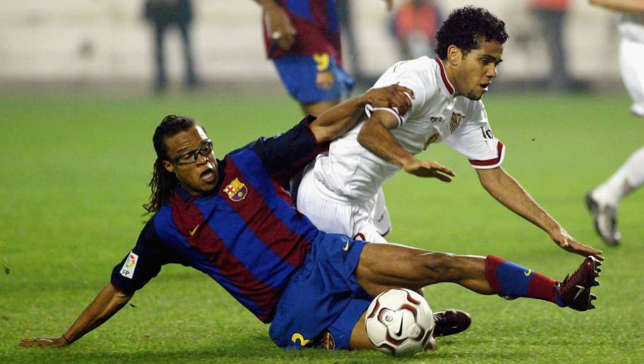 SEVILLA, SPAIN - JANUARY, 25:  Dani Alves of Sevilla is tackled by Edgar Davids of Barcelona during the Spanish Primera Liga match between Sevilla and Barcelona at the Sanchez Pizjuan Stadium on January 25, 2004 in Sevilla, Spain. (Photo by FiroFoto/Getty Images)