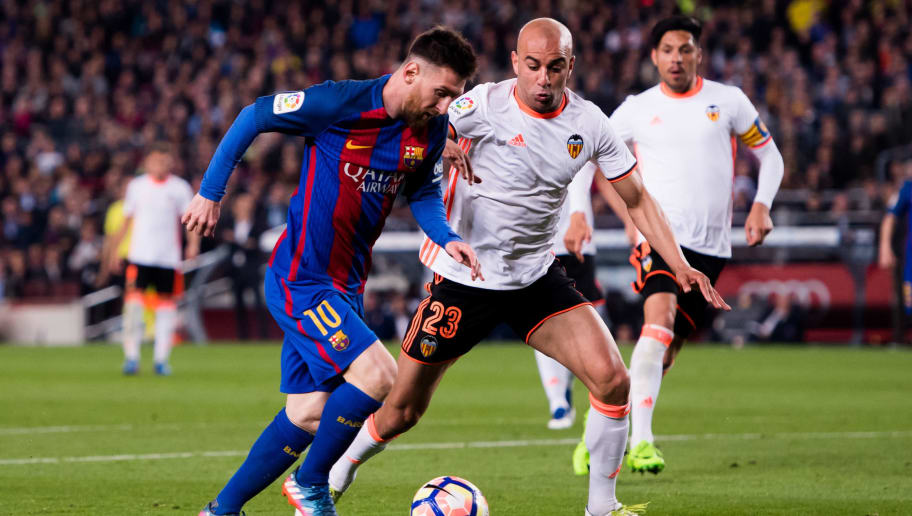 BARCELONA, SPAIN - MARCH 19:  Lionel Messi (L) of FC Barcelona dribbles Aymen Abdennour of Valencia CF before scoring his team's third goal during the La Liga match between FC Barcelona and Valencia CF at Camp Nou stadium on March 19, 2017 in Barcelona, Spain.  (Photo by Alex Caparros/Getty Images)