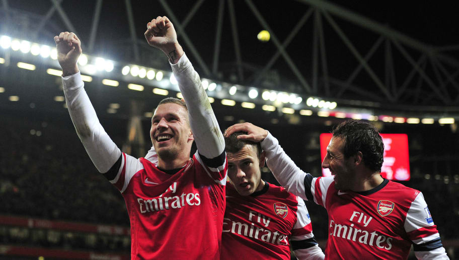 """Arsenal's German striker Lukas Podolski (L) celebrates scoring their third goal during the English Premier League football match between Arsenal and Newcastle United at The Emirates Stadium in north London, England on December 29, 2012. Arsenal won the game 7-3. AFP PHOTO/GLYN KIRK  RESTRICTED TO EDITORIAL USE. No use with unauthorized audio, video, data, fixture lists, club/league logos or """"live"""" services. Online in-match use limited to 45 images, no video emulation. No use in betting, games or single club/league/player publications.        (Photo credit should read GLYN KIRK/AFP/Getty Images)"""