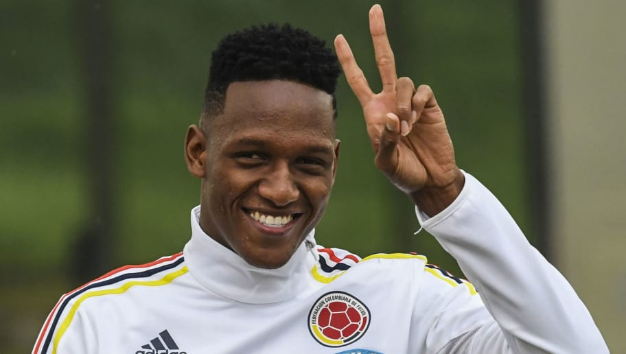 Colombia's defender Yerry Mina makes the 'v' sign to the journalists before a training session at the Colombian football Federation in Bogota on March 25 2017 ahead of their FIFA World Cup South American qualifier football match against Ecuador. / AFP PHOTO / Luis Acosta        (Photo credit should read LUIS ACOSTA/AFP/Getty Images)