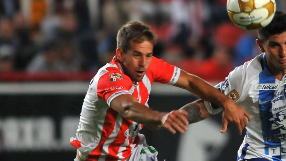 Diego Riolfo (L) of Necaxa vies for the ball with Victor Guzman (R) of Pachuca during the match against Pachuca in their Mexican Apertura 2016 Tournament quarterfinal football match at Victoria stadium on November 24, 2016, in Aguascalientes, Mexico. Necaxa won the mach 2-1. / AFP / VICTOR CRUZ        (Photo credit should read VICTOR CRUZ/AFP/Getty Images)