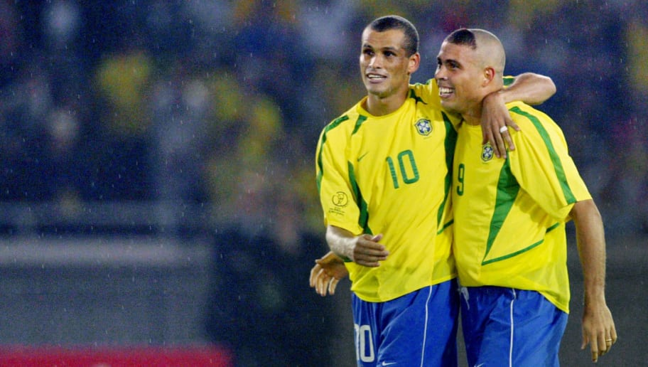 YOKOHAMA, JAPAN:  Brazil's forward Ronaldo (R) and teammate midfielder Rivaldo (L) hug in the rain after Ronaldo scored the second goal against Germany in match 64 of the 2002 FIFA World Cup Korea Japan final 30 June, 2002 at the International Stadium Yokohama, Japan. Brazil won 2-0, giving it a record five World Cup titles.Brazil previously was a FIFA World Cup winner in 1958, 1962, 1970 and 1994. AFP PHOTO PATRICK HERTZOG (Photo credit should read PATRICK HERTZOG/AFP/Getty Images)