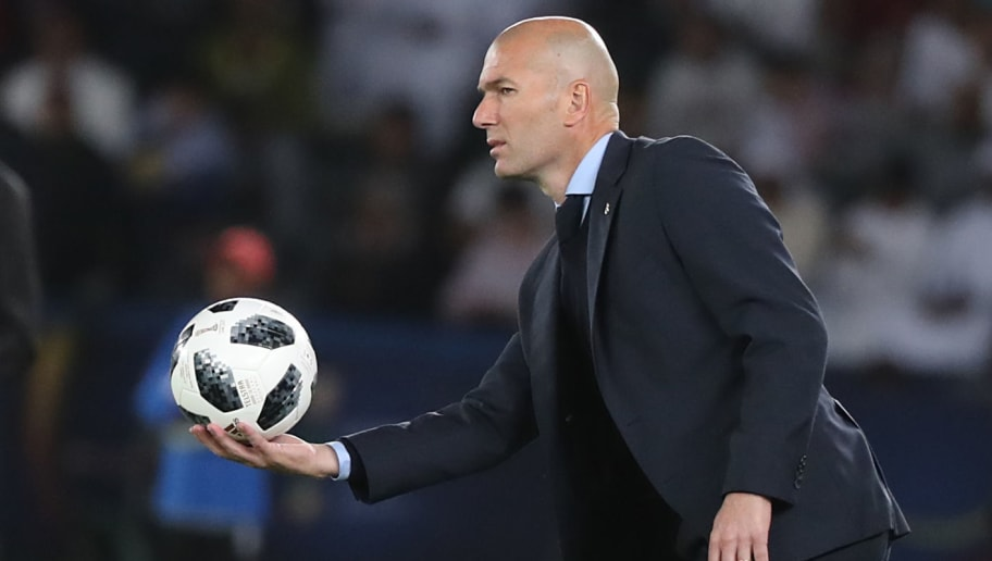 Real Madrid's French coach Zinedine Zidane passes back the ball from on the sidelines during the Club World Cup UAE 2017 final football match between Gremio FBPA and Real Madrid at the Zayed Sports City Stadium in Abu Dhabi on December 16, 2017. / AFP PHOTO / KARIM SAHIB        (Photo credit should read KARIM SAHIB/AFP/Getty Images)