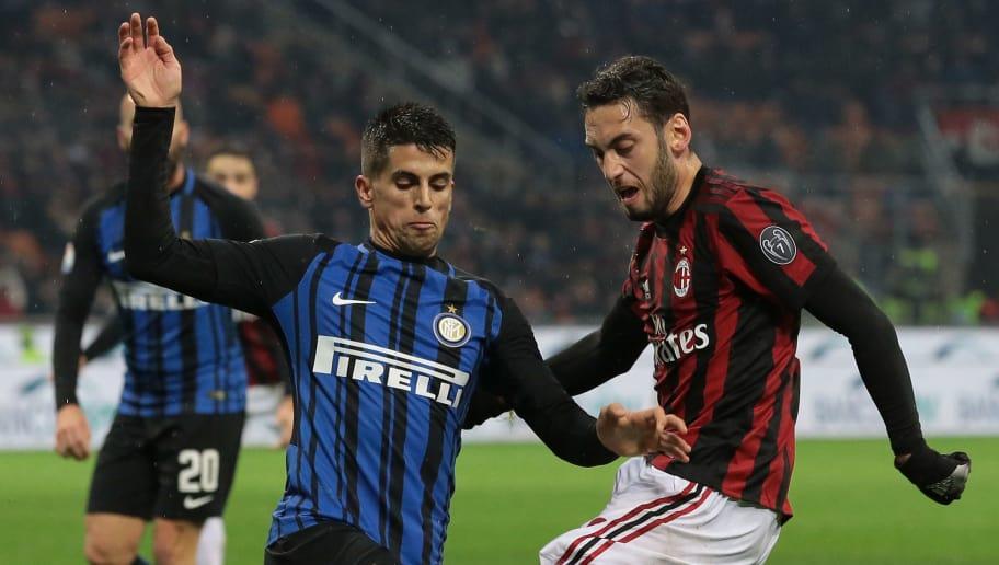 MILAN, ITALY - DECEMBER 27:  Hakan Calhanoglu of AC Milan (R) competes for the ball with Joao Cancelo of FC Internazionale Milano during the TIM Cup match between AC Milan and FC Internazionale at Stadio Giuseppe Meazza on December 27, 2017 in Milan, Italy.  (Photo by Emilio Andreoli/Getty Images)
