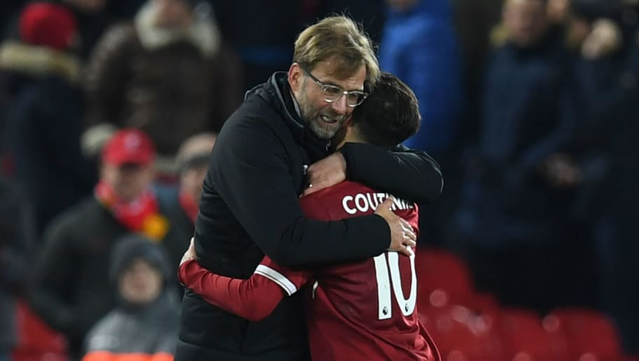 Liverpool's German manager Jurgen Klopp (L) hugs Liverpool's Brazilian midfielder Philippe Coutinho (R) applauds after the final whistle during the English Premier League football match between Liverpool and Swansea City at Anfield in Liverpool, north west England on December 26, 2017. / AFP PHOTO / Paul ELLIS / RESTRICTED TO EDITORIAL USE. No use with unauthorized audio, video, data, fixture lists, club/league logos or 'live' services. Online in-match use limited to 75 images, no video emulation. No use in betting, games or single club/league/player publications.  /         (Photo credit should read PAUL ELLIS/AFP/Getty Images)