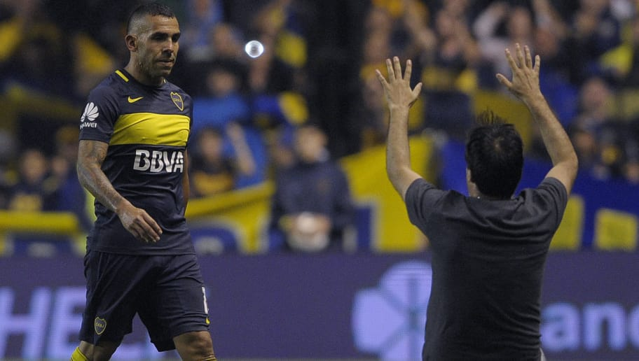 An unidentified fan cheers Boca Juniors' forward Carlos Tevez (L) as he leaves the field during their Argentina First Division football match against Colon at La Bombonera stadium, in Buenos Aires, on December 18, 2016. / AFP / ALEJANDRO PAGNI        (Photo credit should read ALEJANDRO PAGNI/AFP/Getty Images)