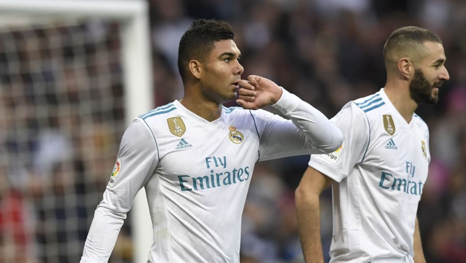 Real Madrid's Brazilian midfielder Casemiro (L) celebrates with Real Madrid's French forward Karim Benzema after scoring during the Spanish league football match Real Madrid CF against Malaga CF on 25, November 2017 at the Santiago Bernabeu stadium in Madrid. / AFP PHOTO / GABRIEL BOUYS        (Photo credit should read GABRIEL BOUYS/AFP/Getty Images)