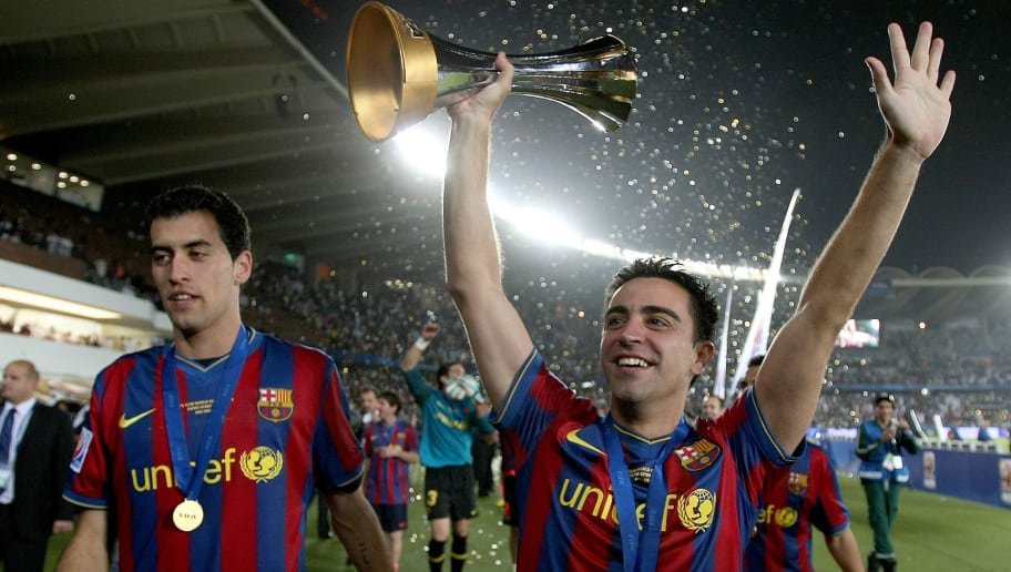Barcelona's Xavi (R) and Sergio Busquets celebrate after winning the 2009 FIFA Club World Cup at Zayed Sports City Stadium in Abu Dhabi on December 19, 2009. Barcelona beat Argentina's Estudiantes de La Plata 2-1 in the final football match. AFP PHOTO/MARWAN NAAMANI (Photo credit should read MARWAN NAAMANI/AFP/Getty Images)