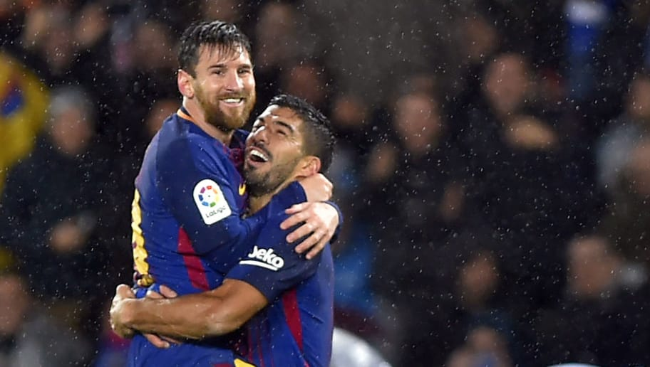 Barcelona's Argentinian forward Lionel Messi (L) is congratulated by teammate Uruguayan forward Luis Suarez after scoring their team's fourth goal during the Spanish league football match between Real Sociedad  and FC Barcelona at the Anoeta stadium in San Sebastian on January 14, 2018. / AFP PHOTO / ANDER GILLENEA        (Photo credit should read ANDER GILLENEA/AFP/Getty Images)