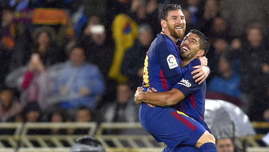 TOPSHOT - Barcelona's Argentinian forward Lionel Messi (L) is congratulated by teammate Uruguayan forward Luis Suarez after scoring their team's fourth goal during the Spanish league football match between Real Sociedad  and FC Barcelona at the Anoeta stadium in San Sebastian on January 14, 2018. / AFP PHOTO / ANDER GILLENEA        (Photo credit should read ANDER GILLENEA/AFP/Getty Images)