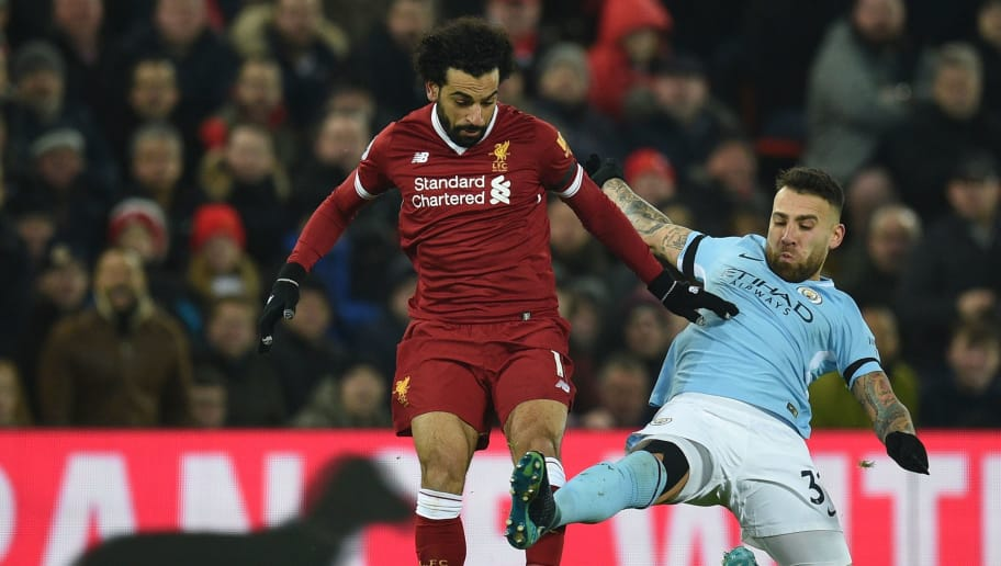 Manchester City's Argentinian defender Nicolas Otamendi (R) tries to tackle Liverpool's Egyptian midfielder Mohamed Salah (L) during the English Premier League football match between Liverpool and Manchester City at Anfield in Liverpool, north west England on January 14, 2018. / AFP PHOTO / Oli SCARFF / RESTRICTED TO EDITORIAL USE. No use with unauthorized audio, video, data, fixture lists, club/league logos or 'live' services. Online in-match use limited to 75 images, no video emulation. No use in betting, games or single club/league/player publications.  /         (Photo credit should read OLI SCARFF/AFP/Getty Images)