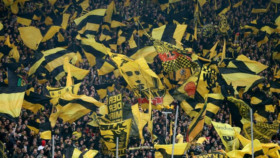 DORTMUND, GERMANY - NOVEMBER 25:  Fans of Dortmund wave flags  during the Bundesliga match between Borussia Dortmund and FC Schalke 04 at Signal Iduna Park on November 25, 2017 in Dortmund, Germany.  (Photo by Christof Koepsel/Bongarts/Getty Images)