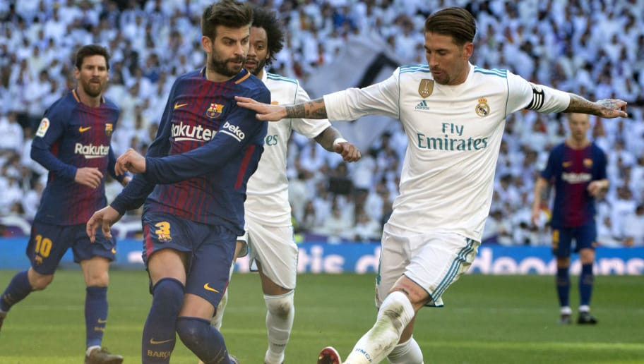 Barcelona's Spanish defender Gerard Pique (L) vies with Real Madrid's Spanish defender Sergio Ramos during the Spanish League 'Clasico' football match Real Madrid CF vs FC Barcelona at the Santiago Bernabeu stadium in Madrid on December 23, 2017.  / AFP PHOTO / CURTO DE LA TORRE        (Photo credit should read CURTO DE LA TORRE/AFP/Getty Images)