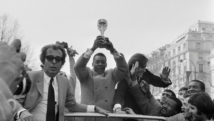 Brazilian soccer star, Edson Arantes do Nascimento, known as Pelé (L), brandishes the World Cup trophy on March 30, 1971 as he walks down the Champs-Elysees avenue in Paris. / AFP PHOTO / -        (Photo credit should read -/AFP/Getty Images)
