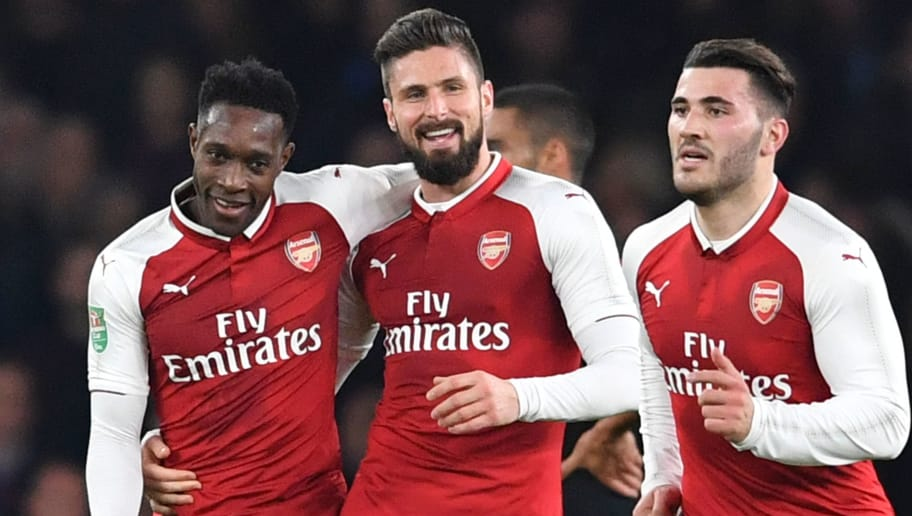 Arsenal's English striker Danny Welbeck (L) celebrates scoring the opening goal with Arsenal's French striker Olivier Giroud (C) during the English League Cup quarter-final football match between Arsenal and West Ham United at the Emirates Stadium in London on December 19, 2017.  / AFP PHOTO / Ben STANSALL / RESTRICTED TO EDITORIAL USE. No use with unauthorized audio, video, data, fixture lists, club/league logos or 'live' services. Online in-match use limited to 75 images, no video emulation. No use in betting, games or single club/league/player publications.  /         (Photo credit should read BEN STANSALL/AFP/Getty Images)