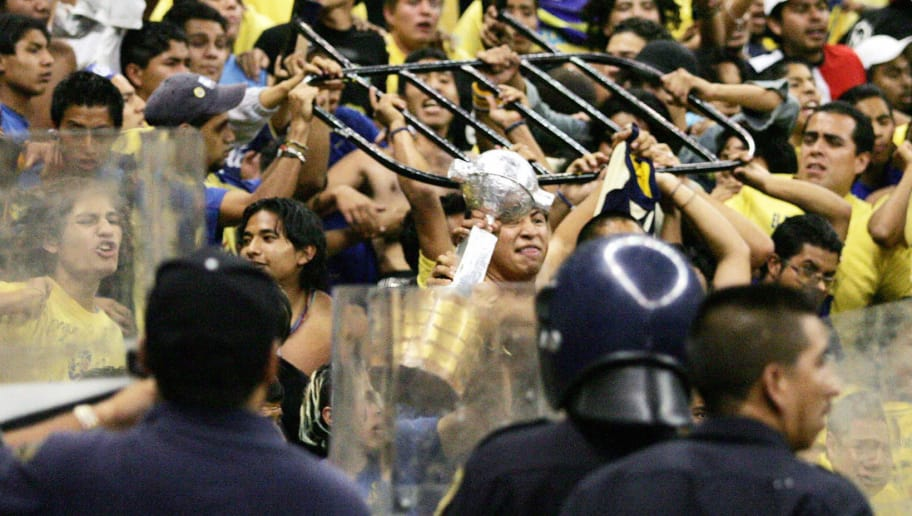 MEXICO CITY, MEXICO:  Mexicans fans try to throw a fence ao anti riot police at the end of the Libertadores Cup soccer match between Mexican America and Brazilian Sao Caetano in Mexico City, 11 May 2004. Sao Cateano qualified for the quarterfinals of the Libertadores Cup AFP PHOTO/Omar TORRES  (Photo credit should read OMAR TORRES/AFP/Getty Images)