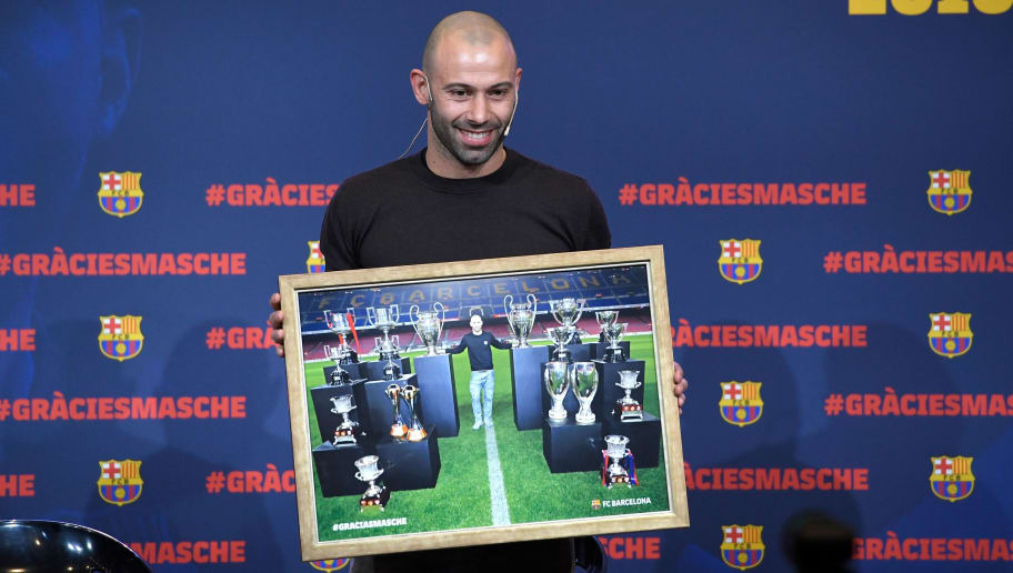 TOPSHOT - Barcelona's Argentinian defender Javier Mascherano poses with a framed picture of him and the major trophies he won with the football club during a farewell ceremony in Barcelona ahead of his transfer to China on January 24, 2018. Mascherano was unveiled as the latest big name to move to China, signing for Hebei China Fortune from Barcelona. / AFP PHOTO / LLUIS GENE        (Photo credit should read LLUIS GENE/AFP/Getty Images)