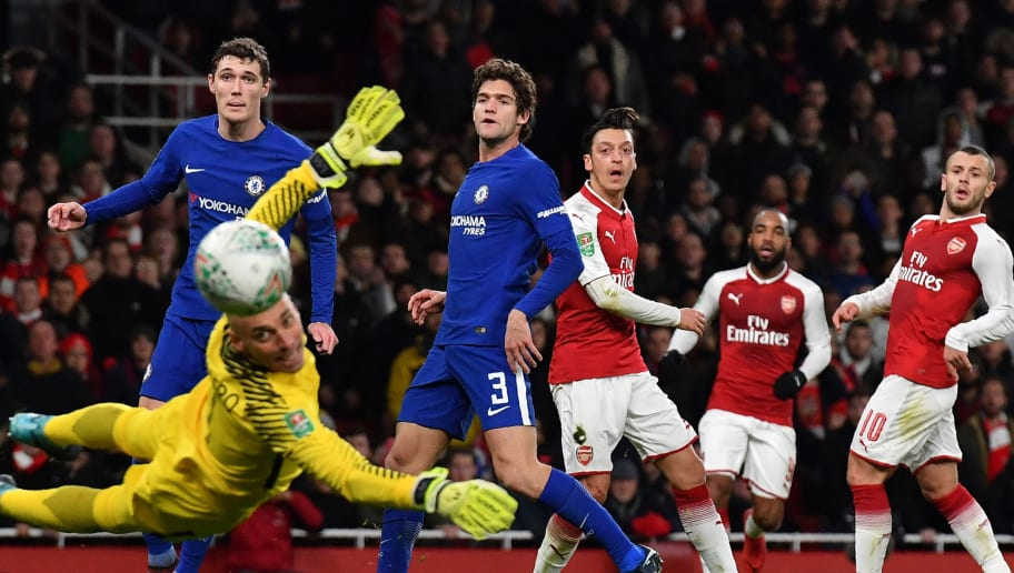 Arsenal's German midfielder Mesut Ozil (C) watches as he misses a shot at goal as Chelsea's Argentinian goalkeeper Willy Caballero (L) dives during the League Cup semi-final football match between Arsenal and Chelsea at the Emirates Stadium in London on January 24, 2018.  / AFP PHOTO / Ben STANSALL / RESTRICTED TO EDITORIAL USE. No use with unauthorized audio, video, data, fixture lists, club/league logos or 'live' services. Online in-match use limited to 75 images, no video emulation. No use in betting, games or single club/league/player publications.  /         (Photo credit should read BEN STANSALL/AFP/Getty Images)